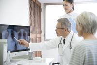 レントゲン写真を見る医者と看護師とシニア女性患者