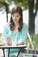 カフェでスマホを見てランチする女性