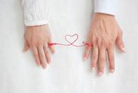 男女の指と指を結んだ赤い糸