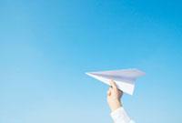 青空と紙飛行機を持つ手