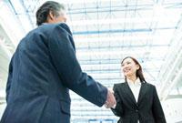 笑顔で握手をするビジネスマンとビジネスウーマン