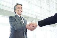 笑顔で握手をする日本人シニアビジネスマン