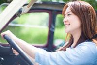 運転席に座りハンドルを握る笑顔の女性