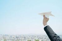 紙飛行機を持つビジネスマンの手と街並