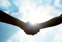 握手する2人の手と太陽