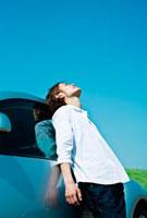 自動車にもたれて空を見上げる男性