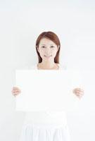 メッセージボードを持つ笑顔の日本人女性
