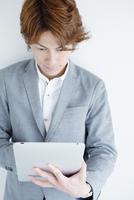 タブレットPCを操作する男性 10250005148| 写真素材・ストックフォト・画像・イラスト素材|アマナイメージズ