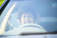 運転席に座る笑顔のシニア女性