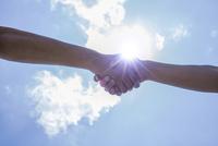 青空と太陽と握手する2人の手