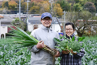 収穫したネギとブロッコリーを持つ農家夫婦