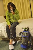 高山病ぎみのため酸素吸入をする女性