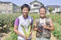 トウモロコシと寺島ナスを手に持つ男性