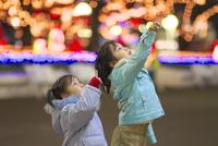 クリスマスイルミネーションの前で上を指差す女の子
