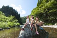 川の中の岩に座る子どもたち