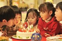 クリスマスケーキのロウソクを消す子供達