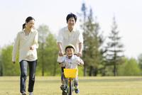 公園で自転車に乗る男の子と一緒に歩く父親と母親 10264005593  写真素材・ストックフォト・画像・イラスト素材 アマナイメージズ
