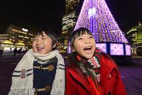 クリスマスツリーの前に立つ女の子と男の子