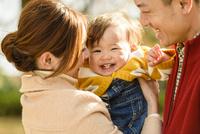 紅葉の公園で赤ちゃんを抱っこするお父さんとお母さん 10264007276| 写真素材・ストックフォト・画像・イラスト素材|アマナイメージズ