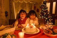 クリスマスケーキの前で並んで座る女の子 10264007379| 写真素材・ストックフォト・画像・イラスト素材|アマナイメージズ