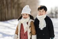 雪の積もる公園で並んで立つ女の子と男の子 10264007744| 写真素材・ストックフォト・画像・イラスト素材|アマナイメージズ