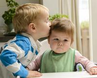 赤ちゃんの頭にキスする男の子