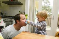 お父さんに牛乳を飲ませてあげる男の子 10264007787| 写真素材・ストックフォト・画像・イラスト素材|アマナイメージズ