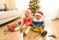 クリスマスツリーの前で並んで座る女の子と男の子