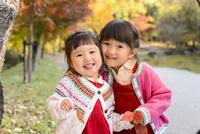 紅葉の公園で並んで笑っているる女の子