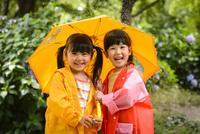 新緑の公園で傘をさして並んでいるレインコートを着た女の子