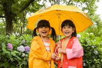 新緑の公園で傘をさして並んでいるレインコートを着た女の子 10264007884| 写真素材・ストックフォト・画像・イラスト素材|アマナイメージズ