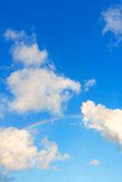 青空に浮かぶ白い雲に架かる虹のアーチ