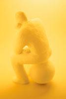 座って考えるクレイ人形 黄色