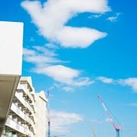 集合住宅ベランダから望む青空とクレーン