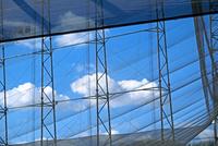 ゴルフ練習場のネット越しに見る青空と白い雲