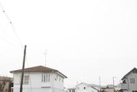 曇天の下に広がる郊外住宅地の白い家