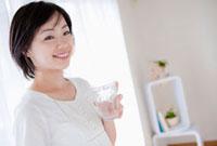 窓際でコップを持った日本人女性