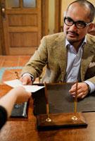 カウンターで書類を渡す日本人男性