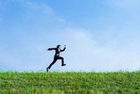 土手をジャンプする日本人のビジネスマン
