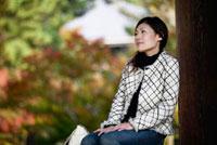 壁にもたれて座る日本人女性