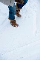 雪の上を歩く日本人女性の足元