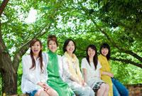 新緑の前に座る日本人の若者