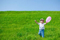 草原で風船を持った日本人の男の子