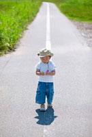一本道に立つ日本人の男の子