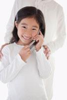 携帯電話を持った女の子と肩に手をおく母親