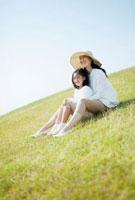 芝生に座る日本人の母と娘