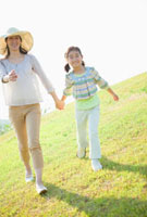 草原を手をつないで歩く日本人の母と娘