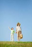 草原で手をつないで立つ日本人の母と娘