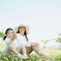 草原に座る日本人の母と娘