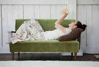 ソファで読書をする日本人女性
